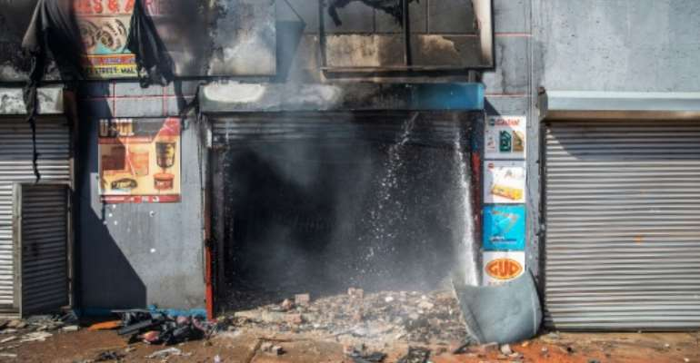 Attacked: The remains of a store in Johannesburg's Malvern area after a night of violence.  By Michele Spatari (AFP)