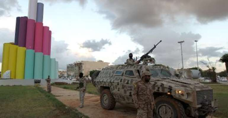Libyan security members stand by an armored personnel carrier as they patrol the streets of Benghazi on November 14, 2013.  By Abdullah Doma (AFP)