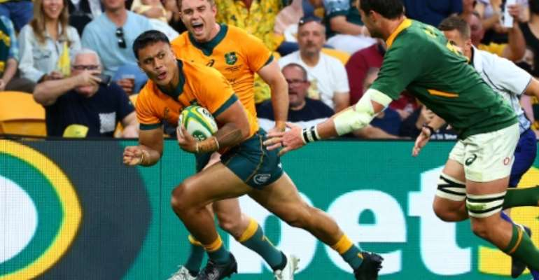 Australia's Len Ikitau scores one of his two tries against South Africa in Brisbane on Saturday.  By Patrick HAMILTON (AFP)