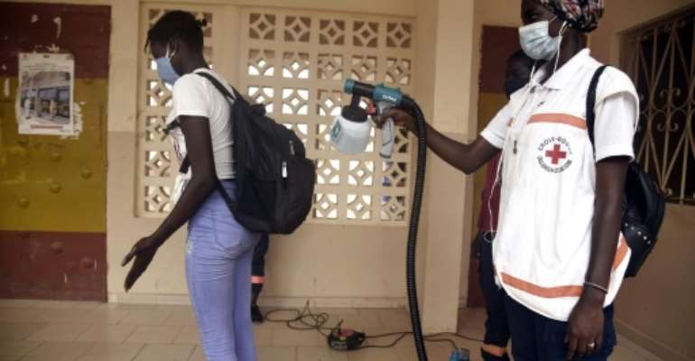 Back to class: A Red Cross worker sprays a pupil with disinfectant at the entrance of a school in Dakar.  By Seyllou (AFP)