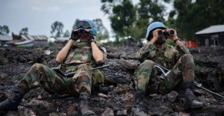 UN peacekeepers look through binoculars at M23 rebel positions on the outskirts of Goma in DR Congo on November 18, 2012.  By Phil Moore (AFP/File)