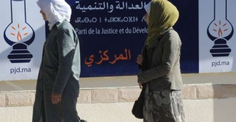 Two veiled members of the Justice and Development Party (PJD) party walk past a PJD campaign poster in Rabat.  By Abdelhak Senna (AFP/File)