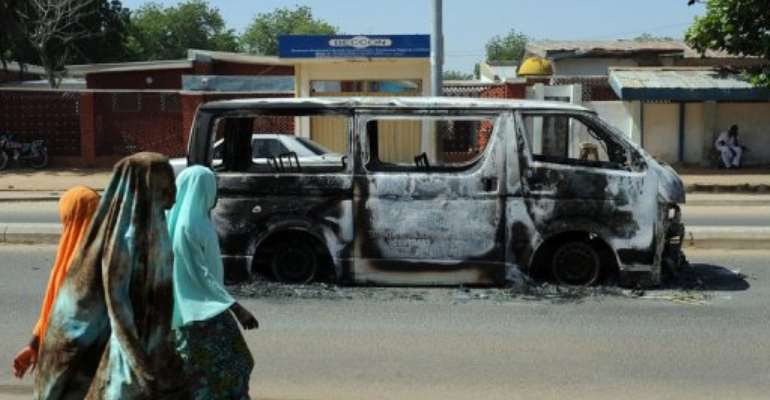 Young girls walk past a vehicle burnt in 2011 on a street in Damaturu in northeastern Nigeria.  By Pius Utomi Ekpei (AFP/File)