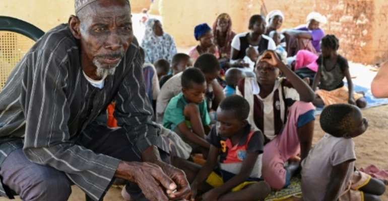 Belem Boureima, a 74-year-old farmer, and his family. They are among the hundreds of thousands of people in Burkina Faso who have fled their homes because jihadist attacks.  By ISSOUF SANOGO (AFP)