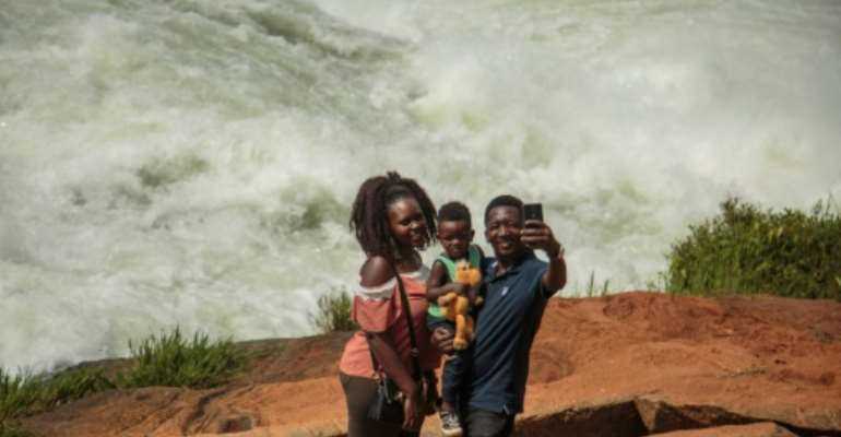 Big river: A family takes a selfie in front of the Nile during the Uganda National Kayaking Championships in Jinja in January. More than 250 people have died in selfie accidents around the world, according to a study published last year.  By Sumy SADURNI (AFP)