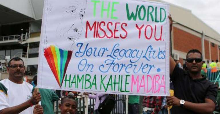 Cricket fans hold a poster paying homage to Nelson Mandela during the one-day international match between India and South Africa in Durban on December 8, 2013.  By Anesh Debiky (AFP)