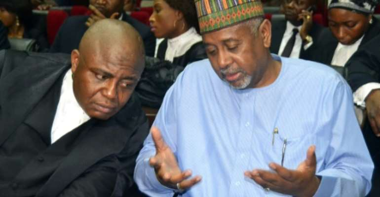 Nigeria's former national security advisor Sambo Dasuki (R), speaks with his lawyer during his trial at the federal high court in Abuja, on September 1, 2015.  By  (AFP/File)