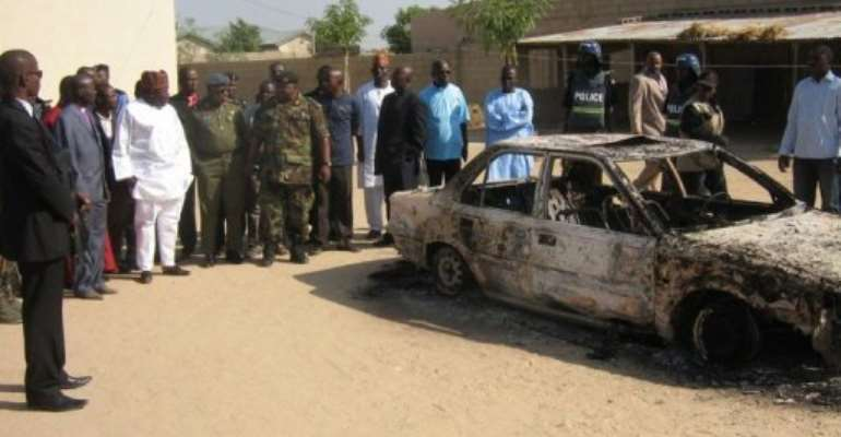 Charred remains of a car in Maiduguri are inspected on December 25, 2010, after Boko Haram had been present in the area.  By Aminu Abubakar (AFP/File)
