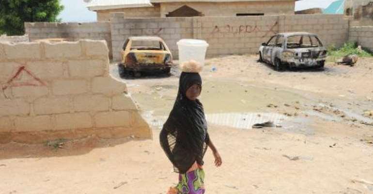 A girl walks past cars burnt by gunmen in Mubi, Nigeria, on October 5, 2012.  By Pius Utomi Ekpei (AFP/File)
