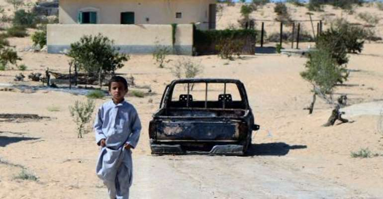 A child walks in front of the wreckage of a burnt car, the day after an attack in a village on the outskirt of the northern Sinai town of Sheik Zuweid on September 10, 2013.  By Mohamed el-Shahed (AFP/File)
