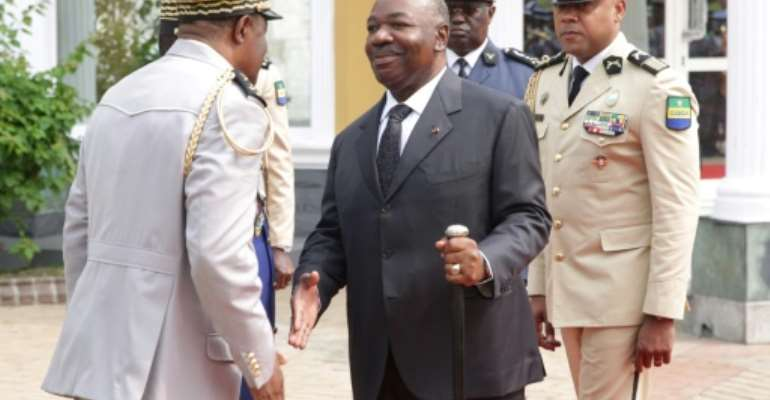 Bongo, centre, shakes hands at a ceremony to honour Gabon's first president.  By STEVE JORDAN (AFP)