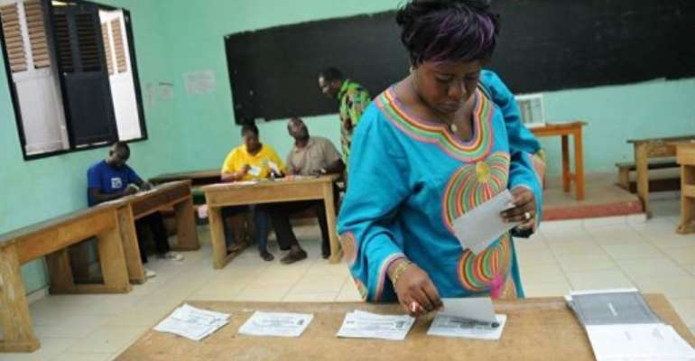 A woman takes ballot papers at a polling station during the legislative elections.  By Wils Yanick Maniengui (AFP/File)