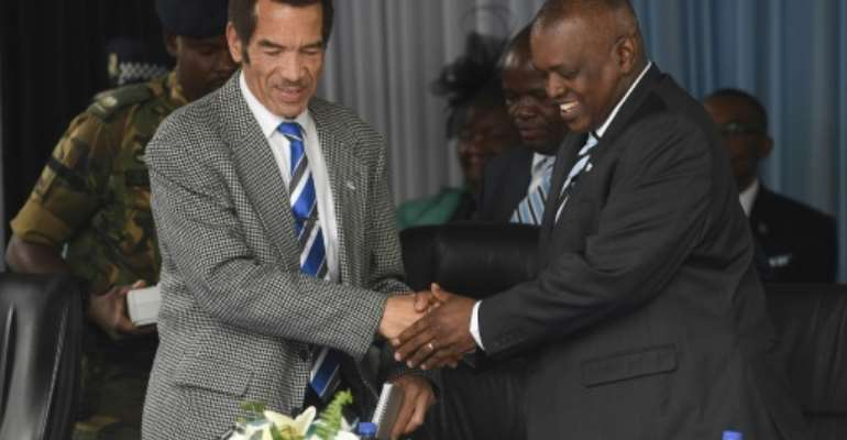 Botswana's former President Ian Khama (L) has accused his successor Mokgweetsi Masisi (R) of becoming autocratic after taking up his post.  By MONIRUL BHUIYAN (AFP)