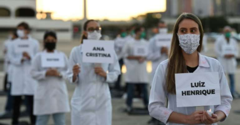 Brazilian nurses honor health workers who have died of COVID-19 during a demonstration in Brasilia.  By EVARISTO SA (AFP)
