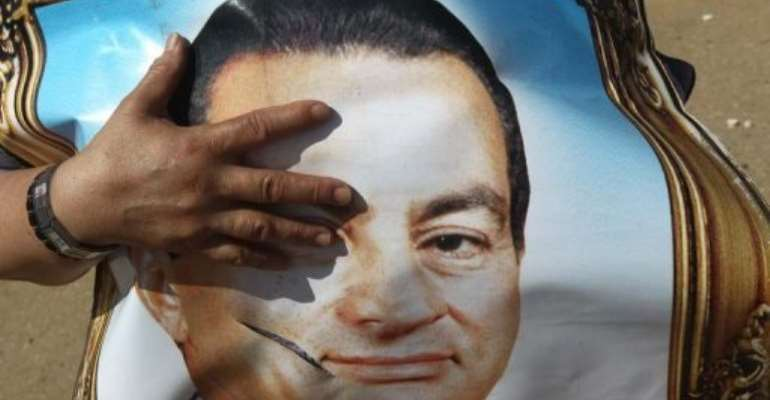 A supporter of Egypt's ousted president Hosni Mubarak holds his portrait outside a courthouse in Cairo in June.  By Khaled Desouki (AFP/File)