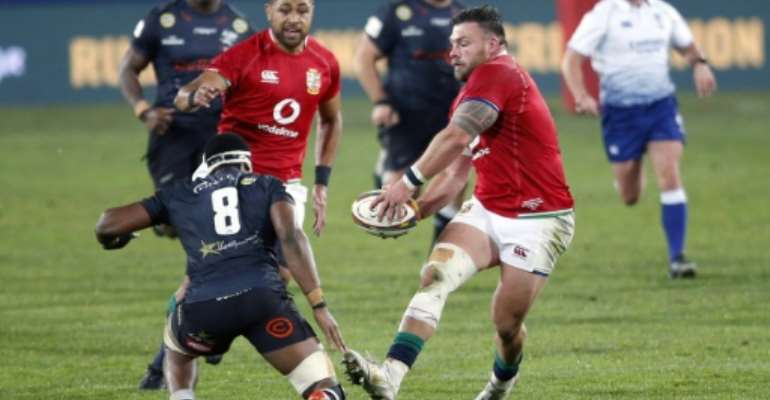 British and Irish Lions prop Rory Sutherland (R) passes the ball during a tour match against the Sharks in Johannesburg on July 7.  By Phill Magakoe (AFP)