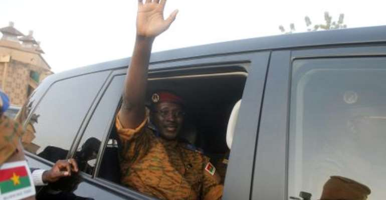 Burkina Faso's army-appointed leader, Lieutenant-Colonel Isaac Zida, waves after signing a transition charter at the Masion du Peuple in Ouagadogou on November 16, 2014.  By  (AFP)