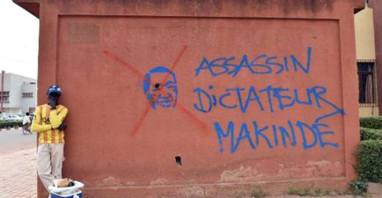 A man stands near graffiti of ousted Burkinabese president Blaise Compaore that reads ''assassin, dictator, Makinde'', on the sidelines of negotiations on the transitional government on November 12, 2014 in Ouagadougou.  By Issouf Sanogo (AFP)