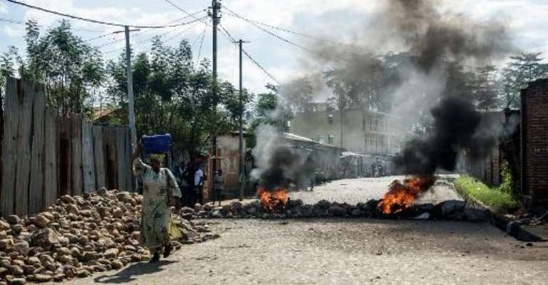 People walk past a burning barricade on a street in Bujumbura after a night marked by gunfire and explosions in various areas of the capital on May 14, 2015.  By Jennifer Huxta (AFP)