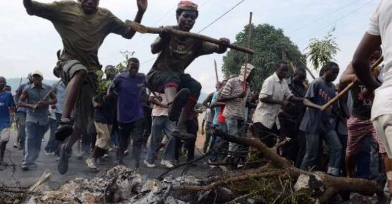 Burundian youth jump over a burning baricade as they demonstrate in Bujumbura, on May 1, 2015 against the president's bid for a third term.  By Simon Maina (AFP)