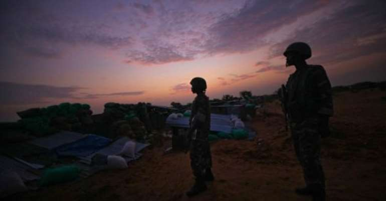 Soldiers serving with AMISOM are seen at daybreak manning frontline positions near Mogadishu in 2011.  By Stuart Price (AFP/AU-UN IST/File)