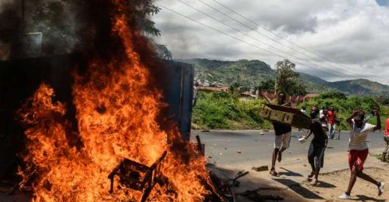 People burn mattresses looted from the local police post in Bujumbura during a protest against incumbent President Pierre Nkurunziza's bid for a thrd term, on May 13, 2015.  By Jennifer Huxta (AFP/File)