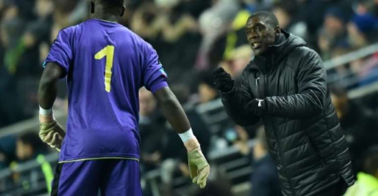 Cameroon coach Clarence Seedorf instructs goalkeeper Andre Onana during a 1-0 friendly loss to Brazil in England last November.  By Glyn KIRK (AFP/File)