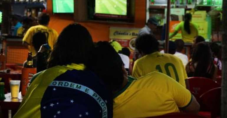 People watch the Brazil v Cameroon match on a television in Porto Seguro, on June 23, 2014, during the 2014 FIFA World Cup.  By Patrik Stollarz (AFP)