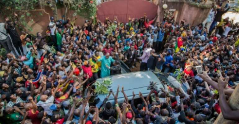 Cameroon's main opposition leader Maurice Kamto was greeted by dozens of cheering, dancing young people on his release from jail.  By STRINGER (AFP)