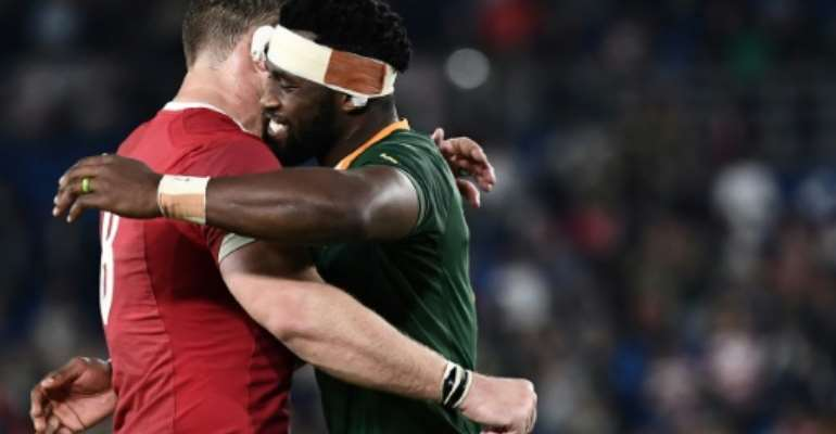 Captain Siya Kolisi (R) hugs teammate Duane Vermeulen, wearing a Wales shirt, after a 19-16 World Cup semi-final victory last Sunday.  By Anne-Christine POUJOULAT (AFP)