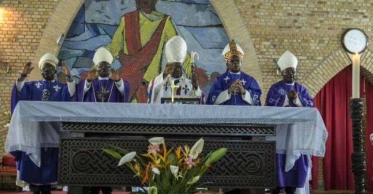 Cardinal Laurent Monsengwo Pasinya (C), Archbishop of Kinshasa and a leading government critic, passed the baton to Fridolin Ambongo, who will take over as de facto leader of the Democratic Republic of Congo's powerful Catholic Church.  By EDUARDO SOTERAS (AFP)
