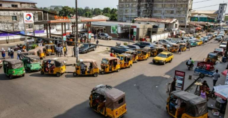 Cars and tuk-tuk taxis often need to wait for hours at fuel stations as Liberia experience petrol a shortage.  By Carielle Doe (AFP/File)