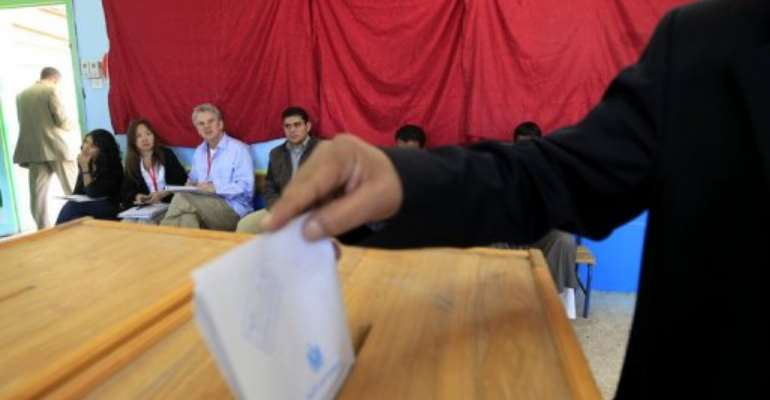 Foreign election monitors watch as an Egyptian casts his ballot at a polling station in Sharm el-Sheikh.  By Mohammed Abed (AFP/File)