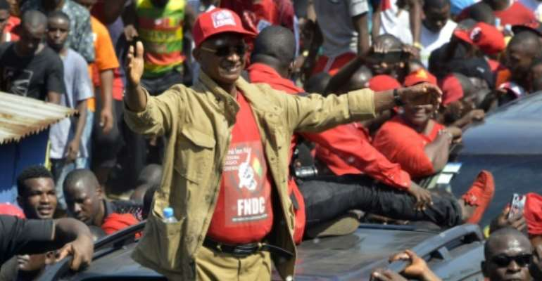 Cellou Dalein Diallo waves to the crowd at a protest against the third term of President Alpha Conde.  By CELLOU BINANI (AFP/File)