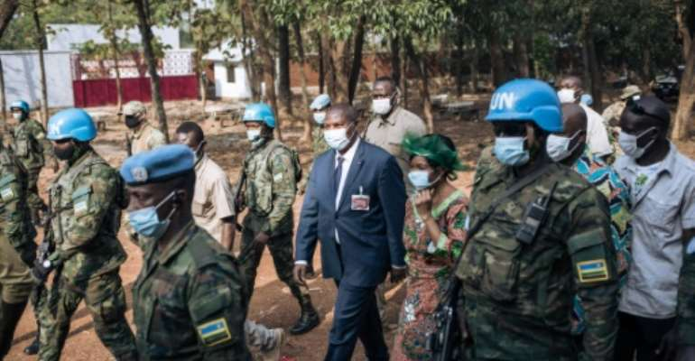 Central African Republic President Faustin Archange Touadera, centre, protected by Rwandan UN peacekeepers on election day last December.  By ALEXIS HUGUET (AFP)
