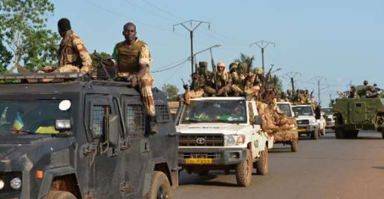 Chadian soldiers sit on a pickup truck as they leave Bangui on April 4, 2014, escorted by African-led MISCA forces.  By Miguel Medina (AFP)