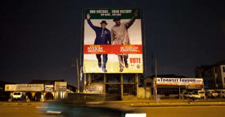 A car passes in street of Part Harcourt, Nigeria, on March 30, 2015, in front of a campaign billboard of incumbent President Goodluck Jonathan.  By  (AFP)