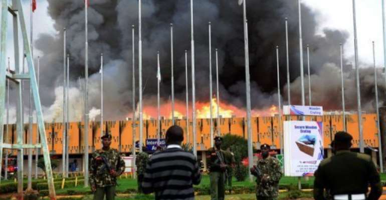 General Service (GSU) officers outside the burning Jomo Kenyatta international airport in Nairobi on August 7, 2013.  By  (AFP)