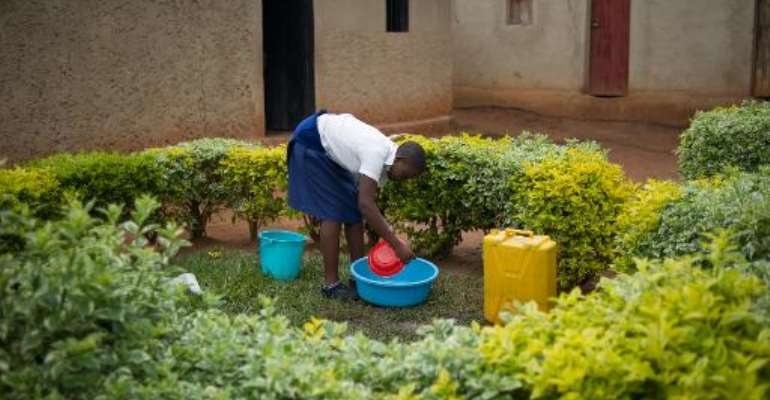 Sofia, 19 year-old daughter of a rape victim, washes utensils outside her home on the outskirts of Kigali, Rwanda on March 14, 2014.  By Phil Moore (AFP)