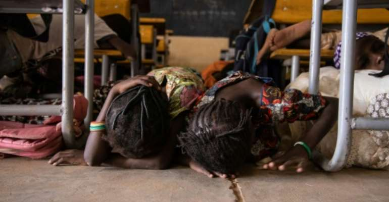 Children hide on the ground during a drill for potential attacks in Burkina Faso, where such assaults have shuttered 3,500 schools.  By OLYMPIA DE MAISMONT (AFP)