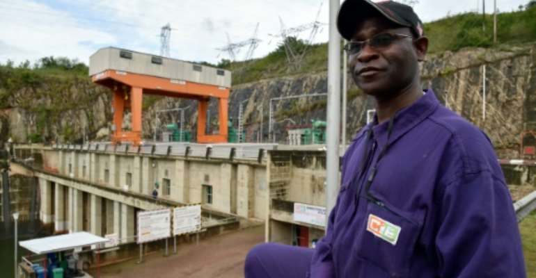 An employee of the Ivorian Electricity Company poses in front of the Kossou dam on September 30, 2014.  By Issouf Sanogo (AFP/File)