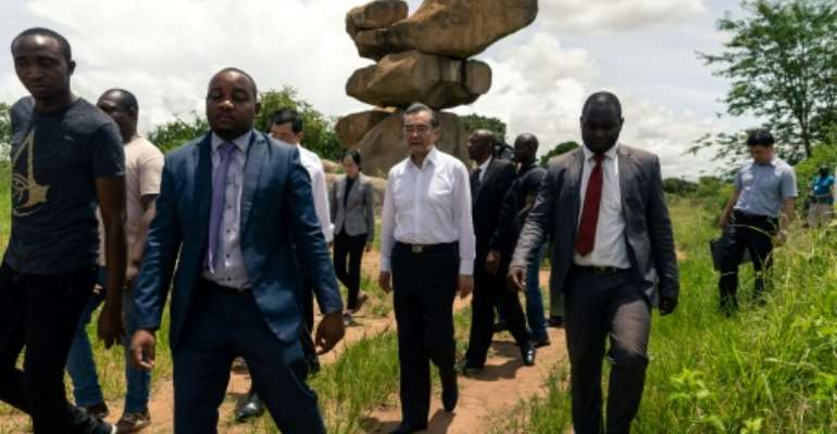 Chinese Foreign Affairs Minister Wang Yi (C) visits the Epworth Balancing Rocks national park in Harare on a visit to Zimbabwe for talks with leaders.  By Jekesai NJIKIZANA (AFP)