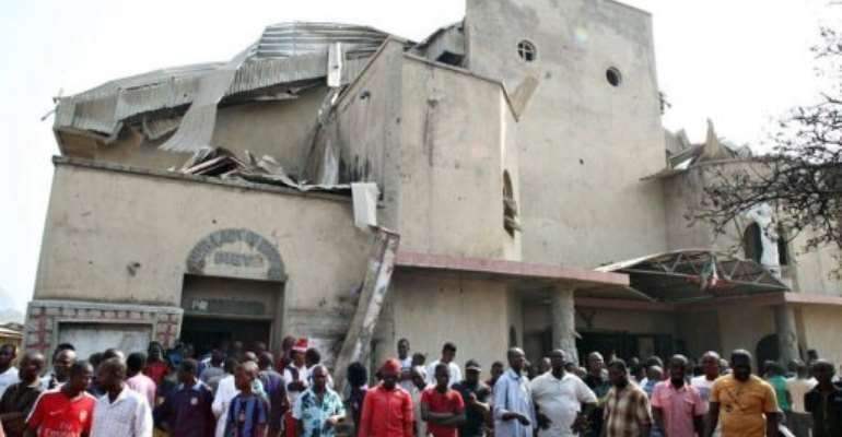 People stand in front of the partially destroyed St Theresa Catholic Church in the Madala Zuba district in Abuja.  By Sunday Aghaeze (AFP)