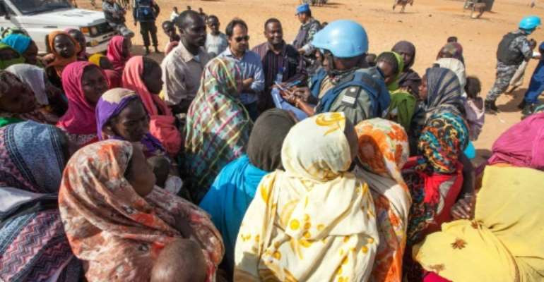 Displaced Sudanese women discuss their concerns with UNAMID personnel at Zam Zam camp for internally displaced people in North Darfur on February 18, 2014.  By Hamid Abdulsalam (UNAMID/AFP/File)