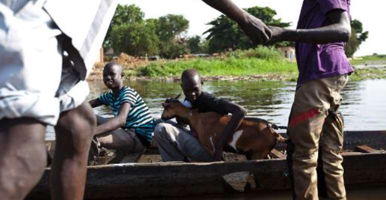 A young boy holds a goat as he prepares to cross the Nam river on a canoe into Tong in Bentiu, South Sudan, on March 23, 2014.  By Ivan Lieman (AFP/File)