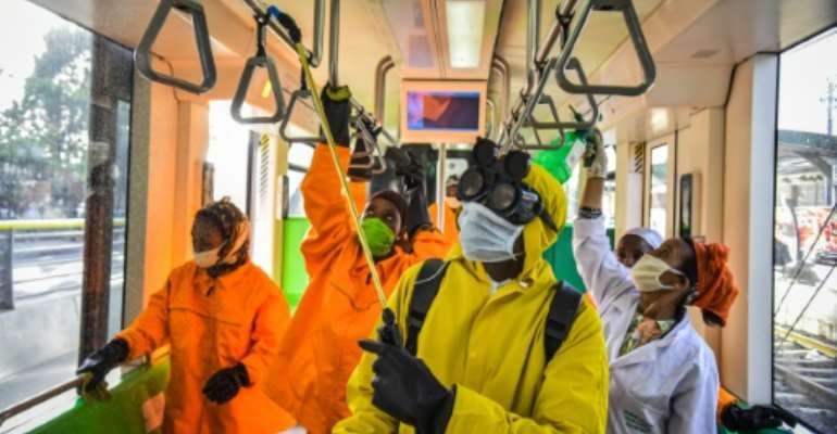 Cleaning staff disinfect a metro carriage in Addis Ababa -- Ethiopia announced its first COVID-19 death Sunday.  By Michael Tewelde (AFP)