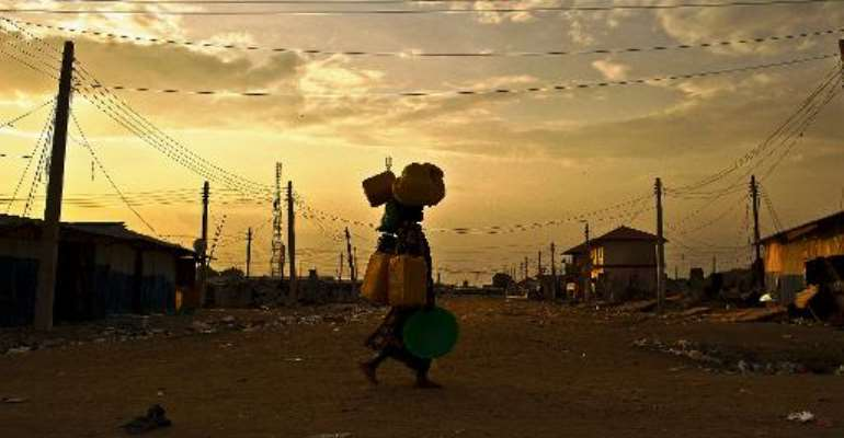 A woman carries belongings through a deserted street in Bor, South Sudan on February 1, 2014.  By Carl de Souza (AFP/File)