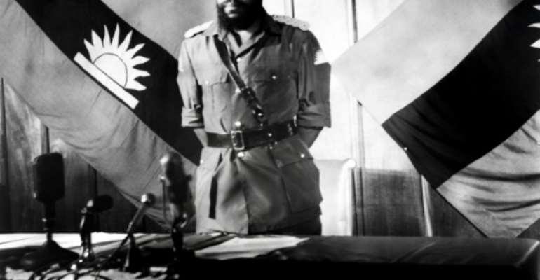 Colonel Chukwuemeka Odumegwu Emeka Ojukwu, the leader of the breakaway Republic of Biafra, stands in front of a Biafra flag.  By - (AFP/File)