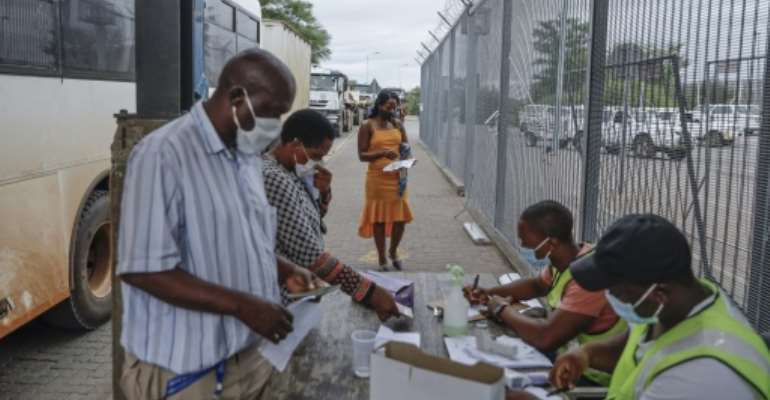 Commuters get COVID-19  test results checked at the South African side of the border -- but a surge in cases is overwhelming authorities on both sides.  By Guillem Sartorio (AFP)