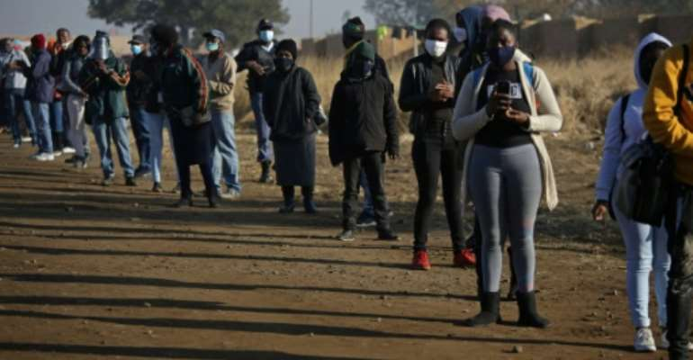 Commuters in South Africa wearing face masks wait outside the Pienaarspoort Station, East of Pretoria to board a train.  By Phill Magakoe (AFP/File)